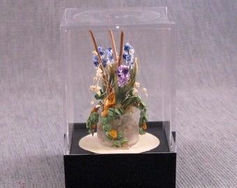 Blue Hyacinth arrangement in a pot all inside an acrylic showcase box