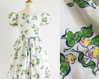 "Vintage 1950s Girls Size 7 Dress / One Piece Cotton Dress / b32 w28 L29"" / Green Leaves Baby Faces Cherub-Like Novelty Print"