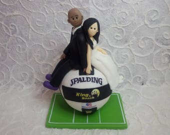 custom bride and  groom sitting on a beachvolleyball wedding cake topper