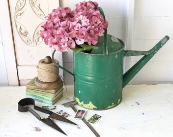 A beautiful vintage chippy paint green watering can