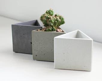 Triangular gray concrete planter with drain hole