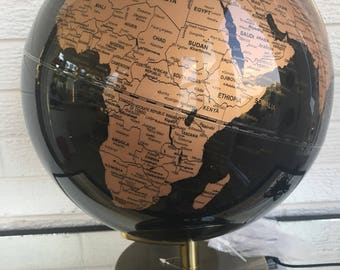 Black and gold illuminated globe lamp  With the flip of a swich this globe lights from within. Detailed map and glossy finish