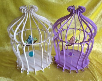 Ornamental bird cage with swinging bird on perch