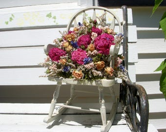 Wooden rocking chair decorated with dried peonies and flowers in Victorian style