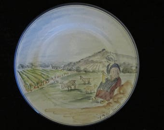 French Decorative Display Plate- hand-painted meadow scene, a sitting maiden knitting while a flock of goats is grazing. Her dog looking on!