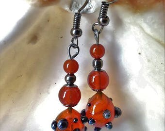 Red-orange glass with small black balls earrings