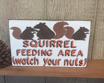 Squirrel Feeding Area (watch your nuts) - Handmade frame less sign, distressed background, hunters orange & black letters w/ squirrels (WH)
