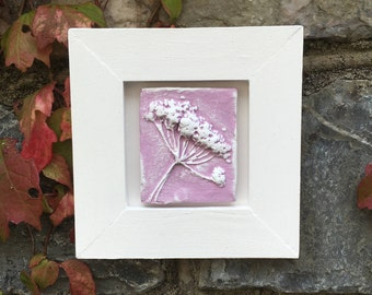 Framed original wall art, rustic clay impression of Queen Anne's Lace seed head, pink and white in a white wooden frame.