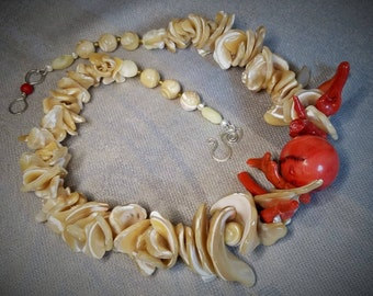 """Coral ball """"hugged"""" by coral branches on a string of sea shells"""