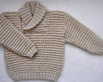 Hand knit baby sweater with shawl neck.