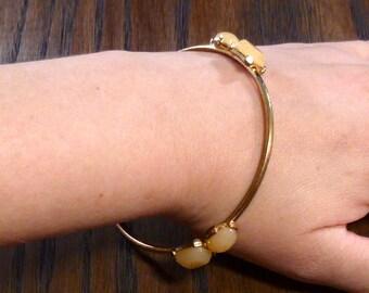 Gold toned bangle bracelet with beige cabochons