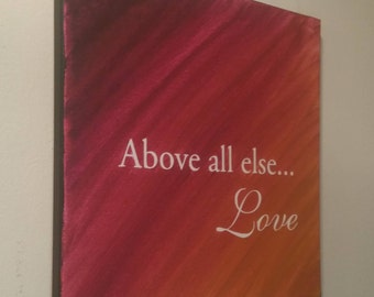 Above all else... Love.saying painting in pink/yellow ochre w/ white lettering