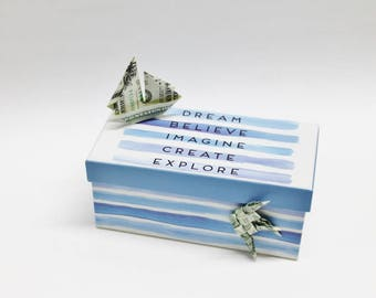 Money Origami Sailboat and fish using 3 one dollar bills on blue striped box with words Dream Believe Imagine Create Explore