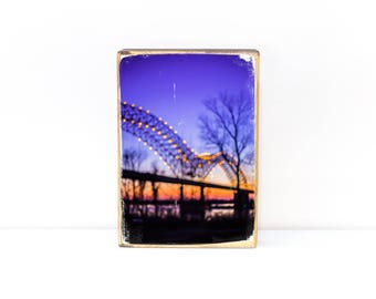 Bridge over Mississippi River in downtown Memphis at night, purple, coral and peach sunset bokeh light photography on wood art