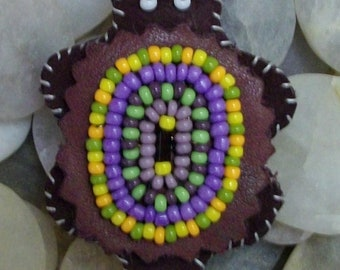 Stylized beaded turtle using mostly 11/0 Czech seed beads on leather with a leather thong. Grp 2 #11