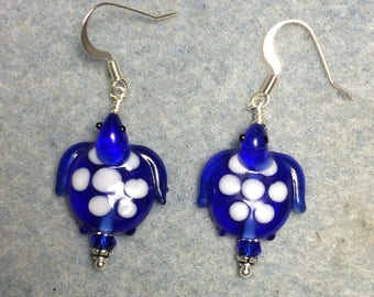Dark blue and white spotted lampwork turtle bead earrings adorned with dark blue Chinese crystal beads.