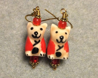 Tan and red ceramic puppy dog dangle earrings adorned with red Czech glass beads.