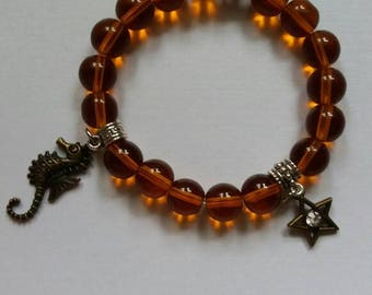 Amber colored glass beads charmed bracelet.