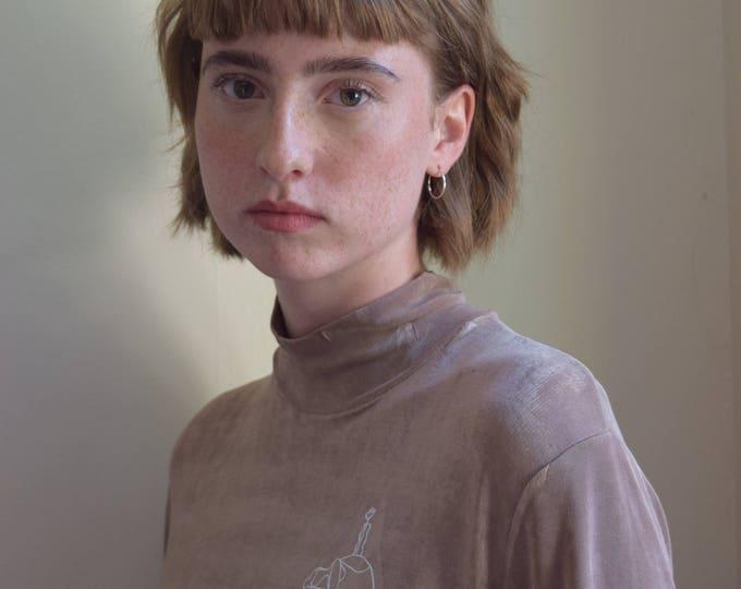 mara b. girl with vase tapioca mock neck.