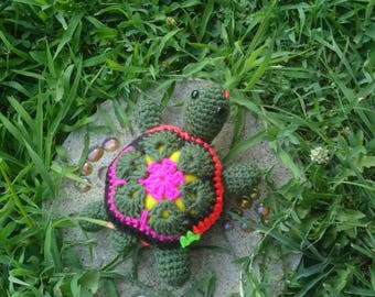 Stuffed little painted turtle. Multi colored yarn on its shell. Green, hot pink, blue etc...