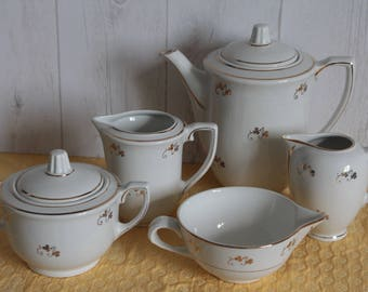 White and gold porcelain coffee service, 20's. SAINT AMAND. France