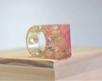 Pink rocks and white flowers encased in a clear Ring