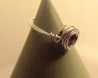 Bezel set silver tone wire wrapped ring with dark red bead