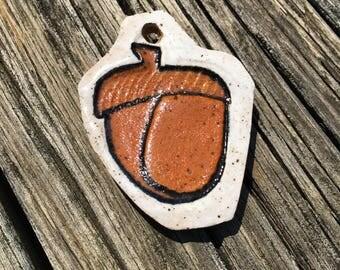 Small ceramic acorn pendant necklace. Stoneware clay pottery.