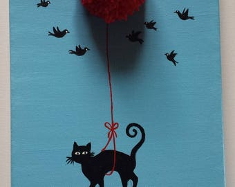 A black cat flies hanging from a red balloon