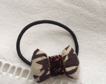 scrunchy with a brown-beige fabric with Brown glittery ribbon bow