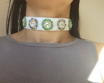 This is a beautiful white velvet choker with sparkly green and silver bicone beads and clear gems sewn onto it.