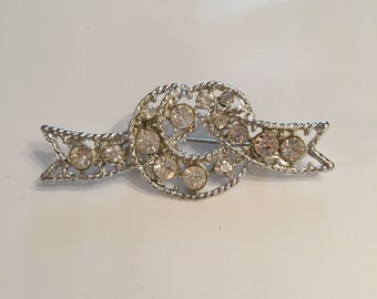 Vintage knot design brooch in a silver tone with clear rhinestones