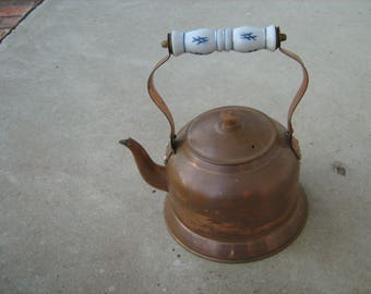 copper tea kettle with blue and white ceramic handle and wood knob