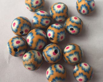 Pack of 14 x 10mm polymer clay round orange with blue and pink coloured flower beads.