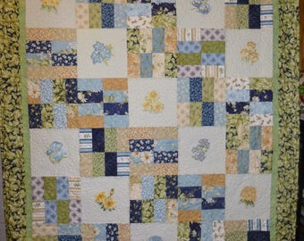 Floral embroidered throw quilt in shades off blue and yellow
