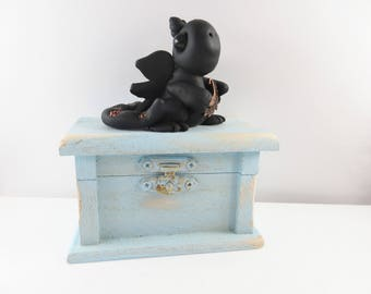 Polymer clay baby dragon on old light blue chest