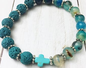 Turquoise lava stone and teal faceted agate elastic bracelet with a petite howlite cross by Jules Jewelry Box