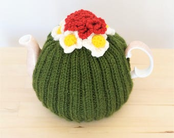 Green tea cosy with red, yellow and white flowers, tea cozy