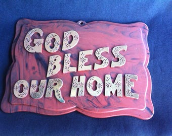 A Small Plastic Wall Plaque With Raised Lettering That Reads God Bless Our Home