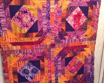 "Bright purple, orange, pink cotton quilt on one side, Other bright red floral, green, blue, 49"" x 49"", 100 percent cotton, machine quilted"