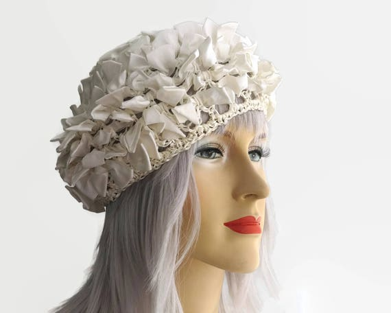 Open weave straw beret covered with ribbon bows, ivory color, very stretchy, uncrushable, will fit any head, circa 1960s