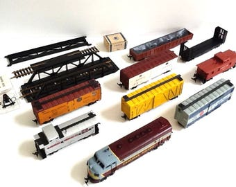 1950's Revell HO Electric Trains & Parts Comprised of 1 Diesel Locomotive, 8 Trains, Bridge, Atlas Rerailer, Bumper and Box of Spikes