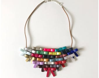 All the bows. Handmade multicolor polymer clay bow breastplate hung on brown suede cord.