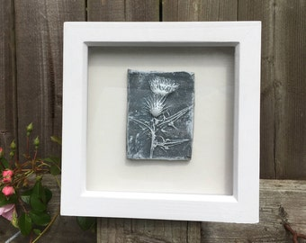 Framed original wall art, raised clay impression of a thistle, grey and white in a white wooden frame.