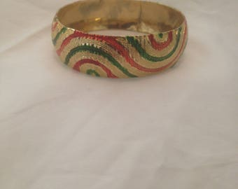 Chunky golden bangle with red and green accents