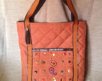 Brown faux leather and orange quilted canvas tote bag.