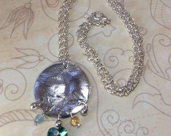 Silver plated hammered disc pendant with vitrial Swarovski hearts, yellow citrine and aqua jade beads