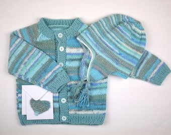 Baby cardigan, hand knitted in blue fair isle effect yarn. Matching hat pulls on with tassels. Gift card included