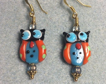 Red and blue lampwork owl bead earrings adorned with blue Czech glass beads.