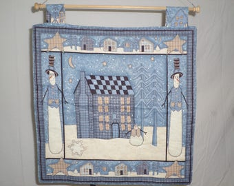 Snowman handmade wallhanging blue and cream 16 1/2 by 17 inches has snowman houses ans stars.